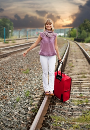 Happy woman with luggage walking on rail photo