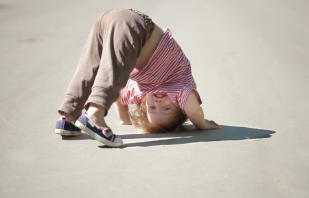 Two-year baby girl playing upside down in street photo