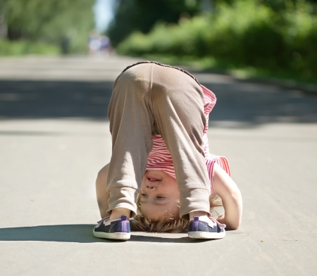 Two-year chid upside down in park photo
