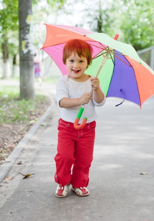 1 2 years: Happy 2 years girl  with umbrella in summer street Stock Photo