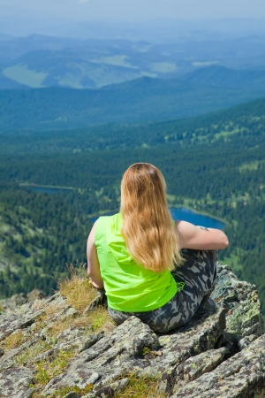 Woman sitting on mountain peak and looking to valley below photo