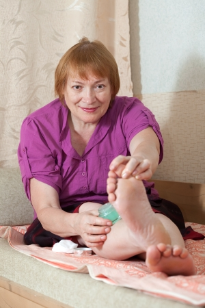 Mature woman caring for the nails on your feet Stock Photo - 14725848