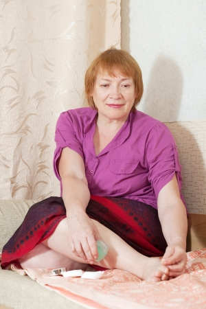 Mature woman treats her toenails Stock Photo - 14725849