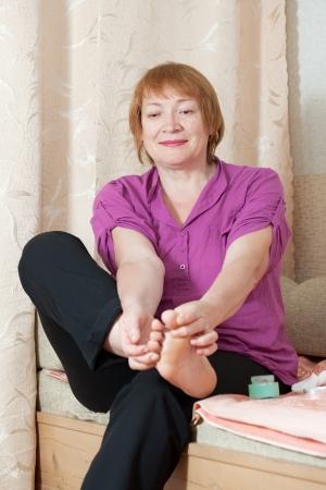 Mature woman treats her toenails photo
