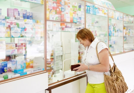 Mature woman buys drugs at the pharmacy photo