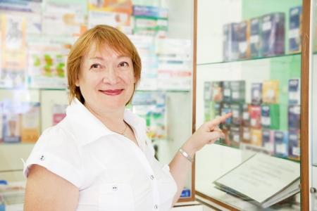 condones: Mujer madura elige a los anticonceptivos en la farmacia