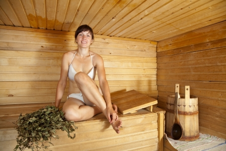 sauna: Young woman  sitting on wooden bench  at sauna   Stock Photo