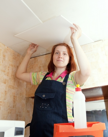 Woman glues ceiling tile at home Stock Photo - 14730588