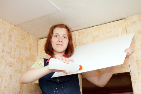 Young woman glues ceiling tile at home photo