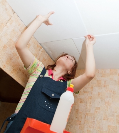soffit cladding: Woman glues ceiling tile at home