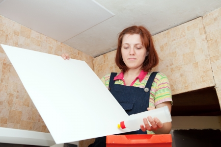 Girl glues ceiling tile at home Stock Photo - 14730593