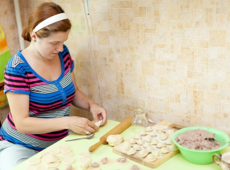 Woman making russian meat dumplings (pelmeni) in her kitchen photo