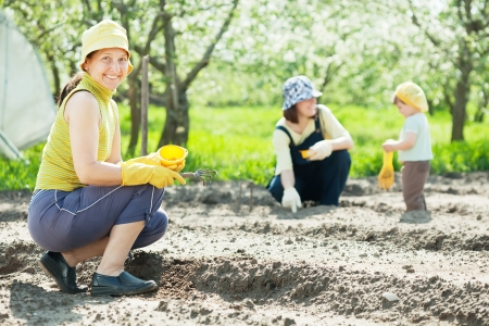 women and kid sows seeds in soil at field Stock Photo - 14741251
