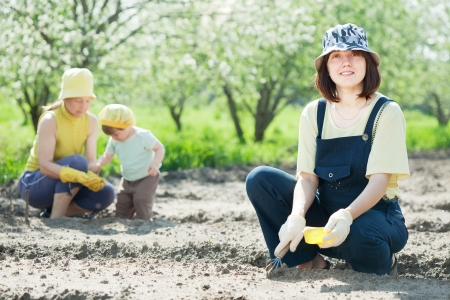 women with child works at garden in spring Stock Photo - 14741242