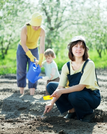 women with child works at garden in spring photo