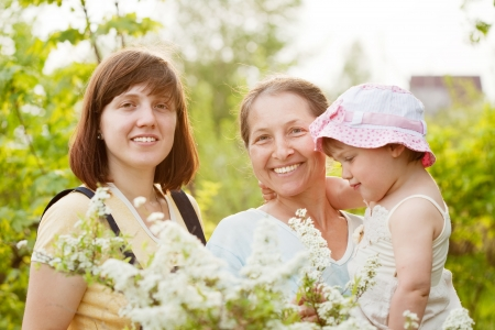 Happy women and kid in plant at summer garden photo