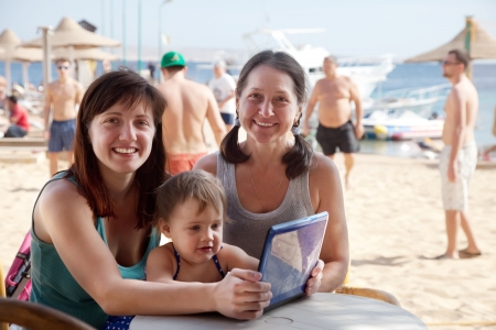 happy family  with laptop  at resort  beach photo