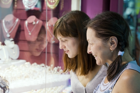 Two women chooses jewelry at shop photo