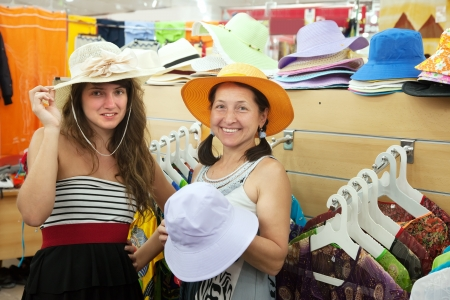 Two women  chooses hat at fashionable shop photo
