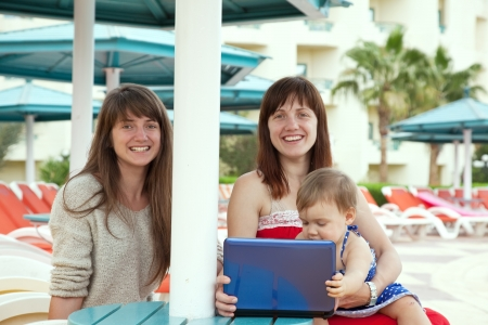 happy girls   sitting  with laptop at resort area photo