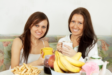 Two smiling women have tea with fruits  in the kitchen photo