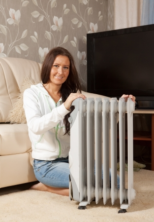 woolley:  smiling woman  near warm radiator  in home Stock Photo