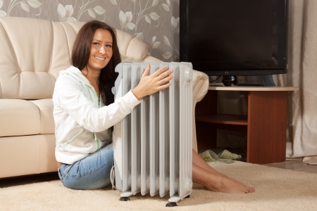 woolley:  smiling woman   near warm radiator  in home
