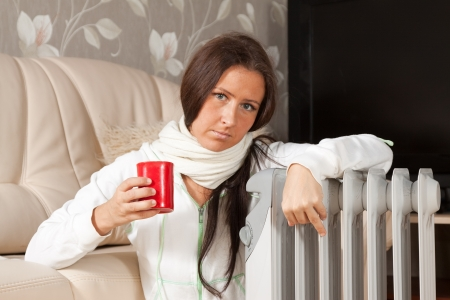 woman  with red cup near oil heater  Stock Photo