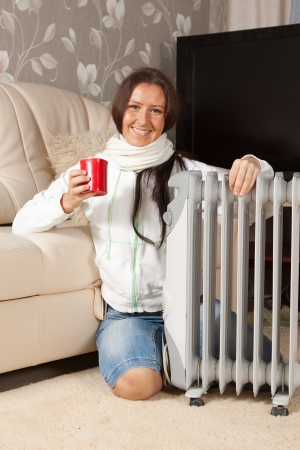 smiling woman  with red cup near oil heater  photo