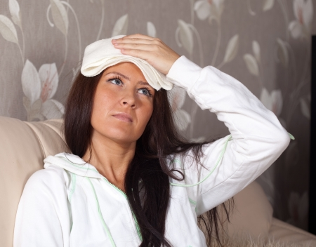 woman having  headache holding towel on her head photo