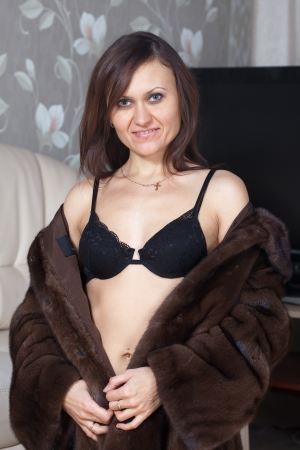 furskin: Sexy woman in fur coat  at home interior Stock Photo
