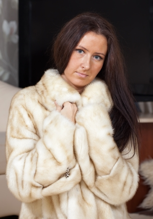 furskin: Portrait of woman  in fur coat  at home interior