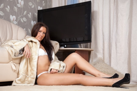 Sexy woman in fur coat  at home interior photo