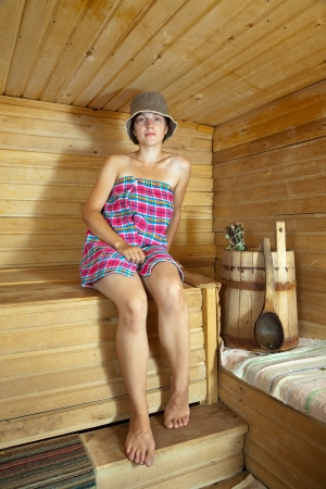 stive: beautiful  woman sitting on wooden bench in sauna