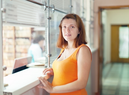 Pregnant woman waiting  for patient's records in clinic reception desk  photo