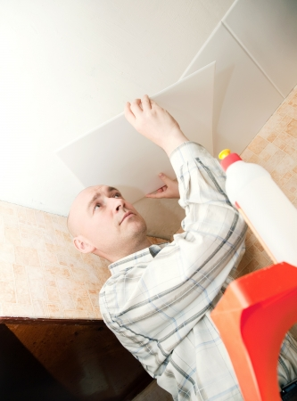 remount: Man glues ceiling tile at home