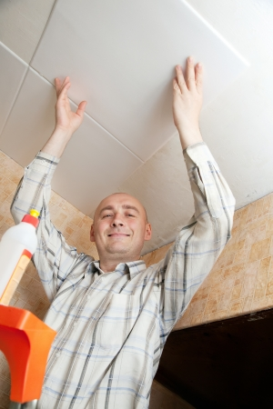 guy glues ceiling tile at home photo