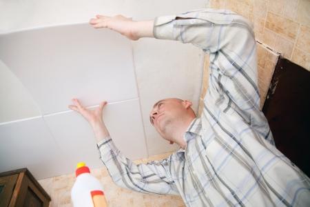 Man glues ceiling tile at home photo
