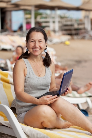one adult: Happy mature woman sitting  with laptop at resort beach