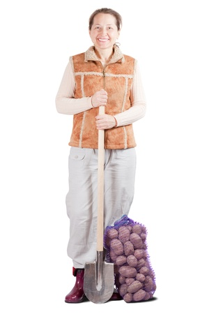 Female farmer  with harvested potatoes and spade over white photo