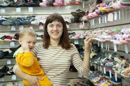 Happy mother with child chooses baby shoes at fashionable shop photo
