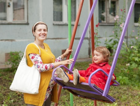 gravida: pregnant  woman with child on swing in autumn park Stock Photo
