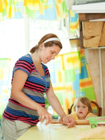 gravida: pregnant woman with child making meat dumplings from stuffing and dough Stock Photo