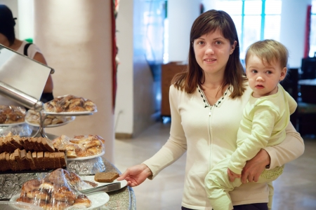 mother with child takes fresh pastry on table in buffet   photo