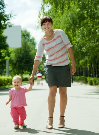toddler walking: mother with happy toddler walking on road