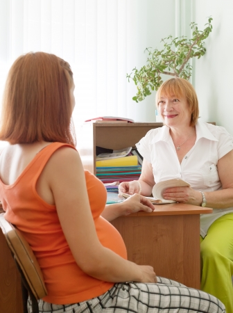 test de grossesse: M�decin d'�ge m�r et une femme enceinte dans une clinique