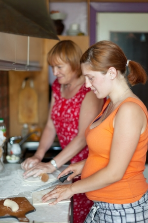 Two women cooks pie with fillings in  kitchen photo