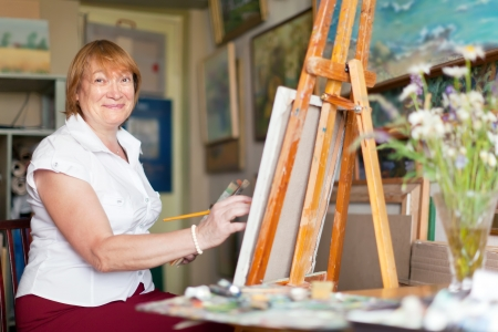 Female artist paints anything on canvas in studio photo