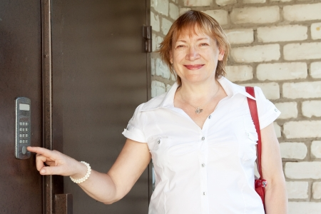 Mature woman pushing button of house intercom  outdoor photo
