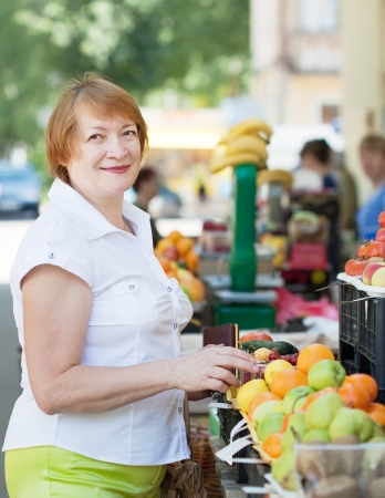 Mature woman  chooses fruits and vegetables at  market photo
